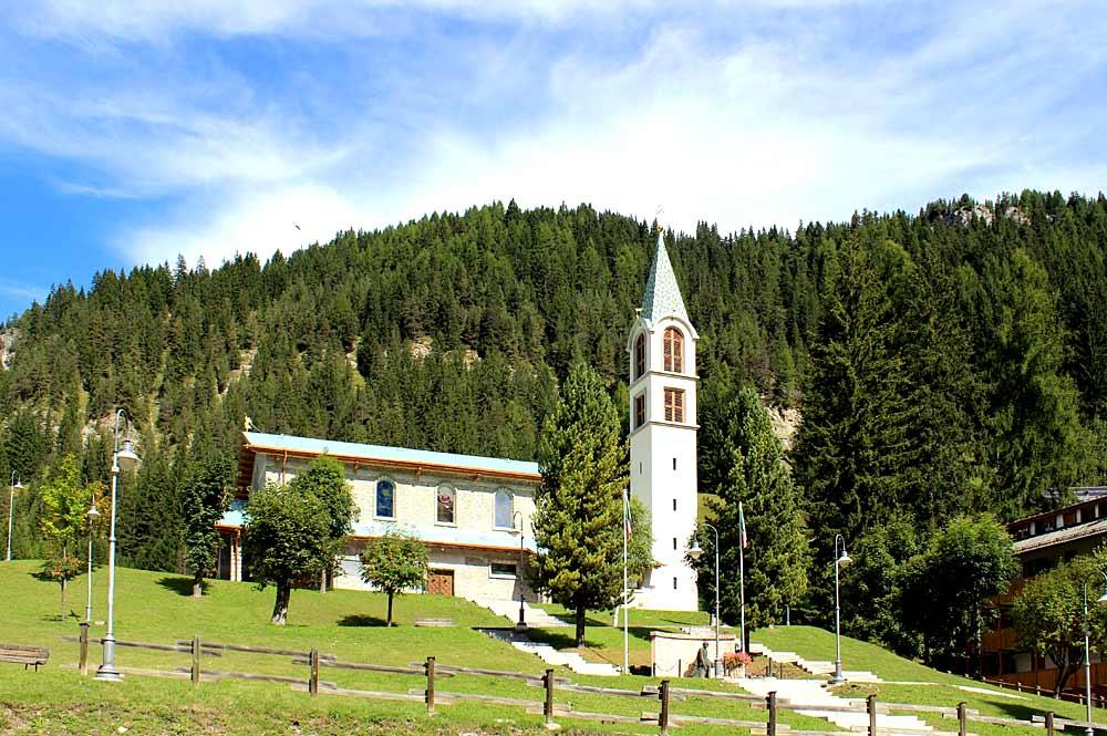 Blick auf die Herz-Jesu-Kirche in Canazei mit ihrem Holzdach