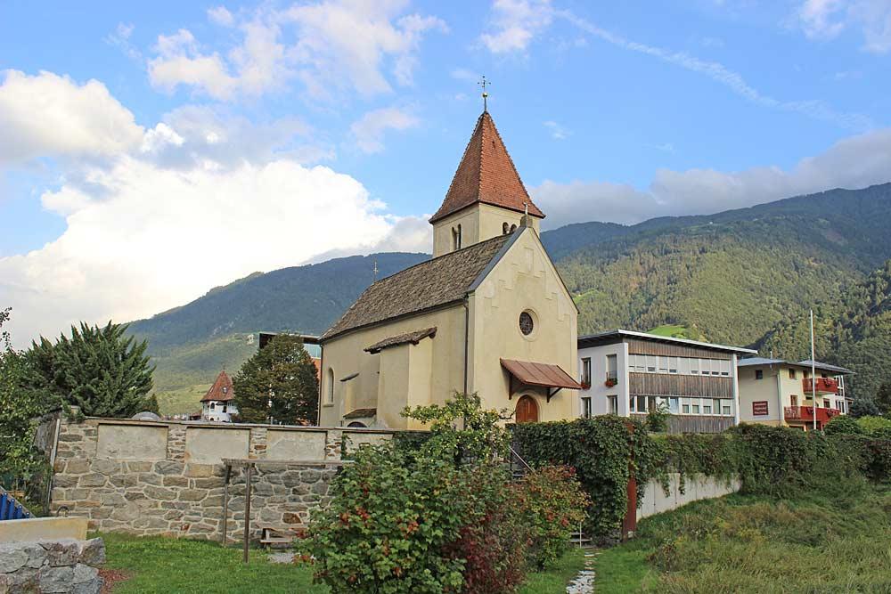 Blick auf die Friedhofsmauer und St. Ulrich in Plaus von Westen aus