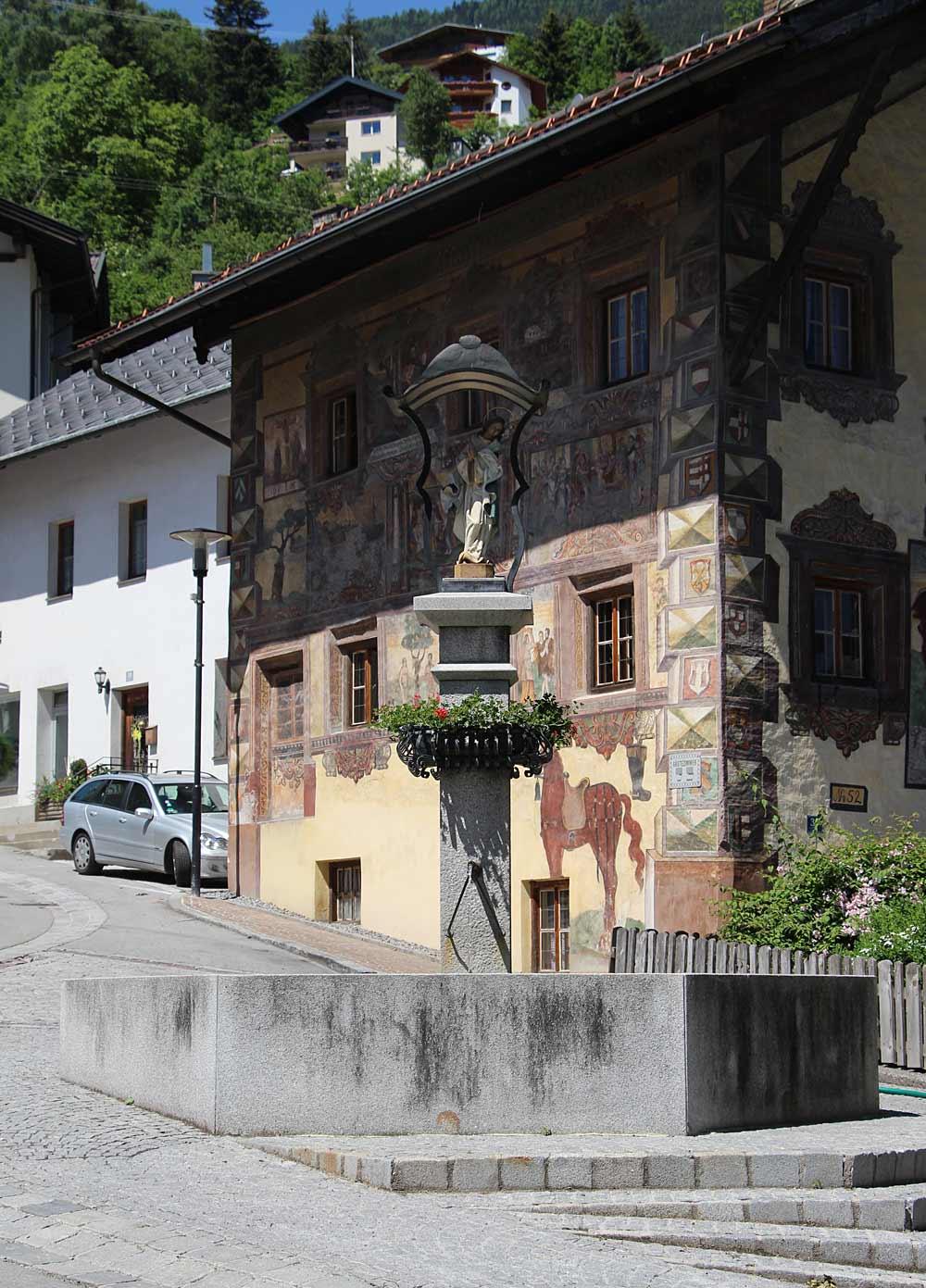 Blick auf den Dorfplatz Wenns mit Marienbrunnen und Platzhaus
