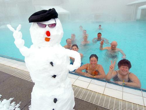 Badegäste im Aussenbecken mit Schneemann im Vordergrund.