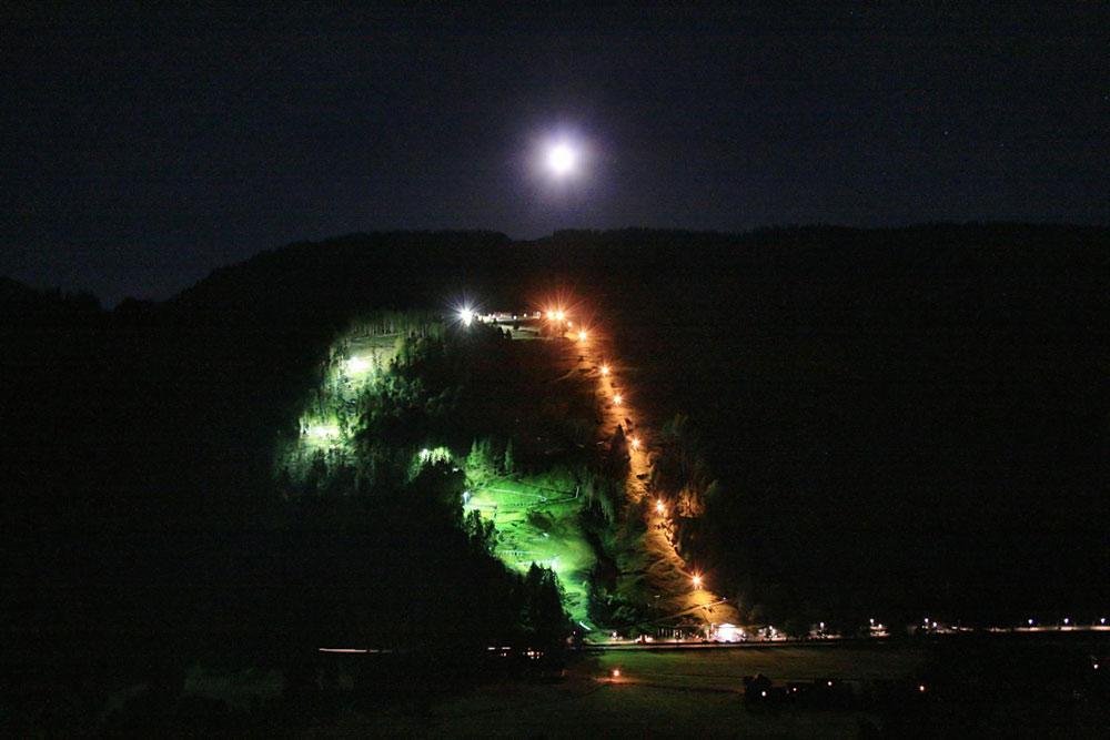 Die Alpsee Bergwelt bei Nacht wird in verschiedenen Farben beleuchtet