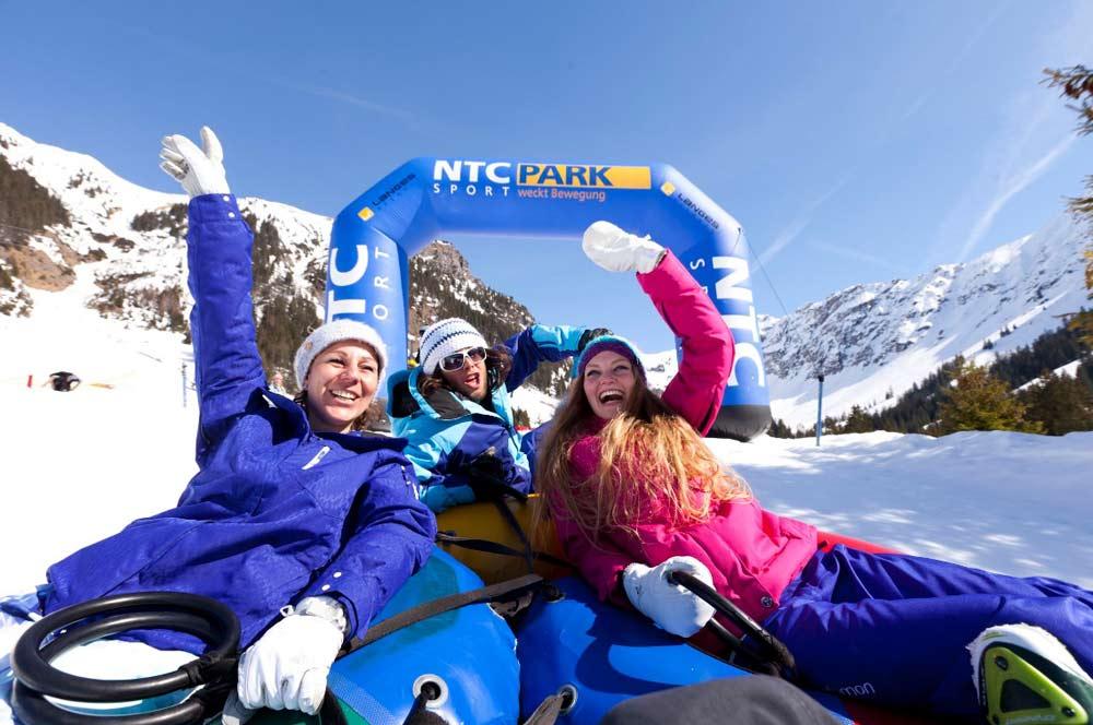 Eine Gruppe Wintersportler beim Snowtubing auf der Piste