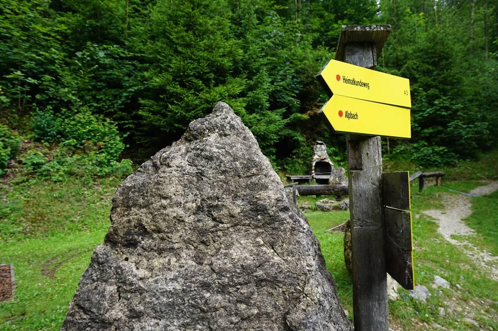 Richtungsschild des Alpbacher Heimatweg mit Grillplatz im Hintergrund