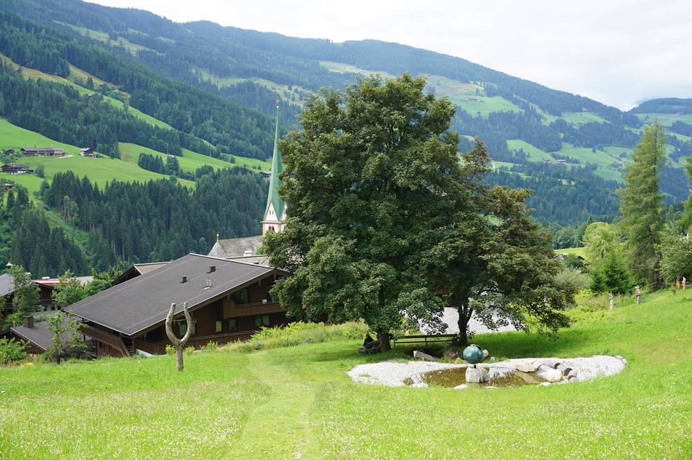 Vorplatz mit altem Baum und Sitzgelegenheit des Ort der Stille in Alpbach