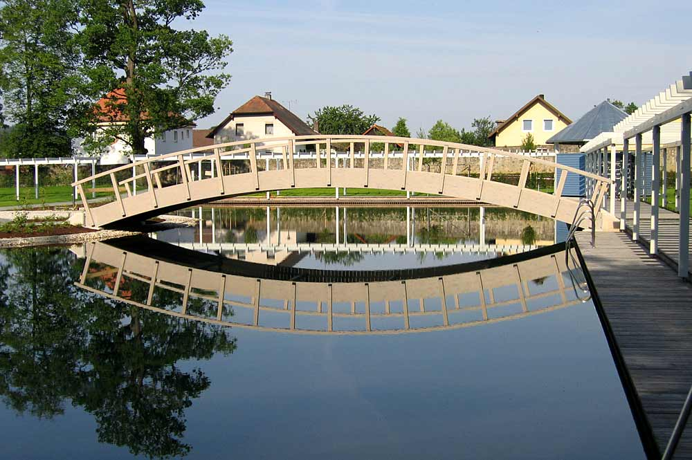 Blick auf die Holzbrücke über das Schwimmbecken im Naturbad Stamsried
