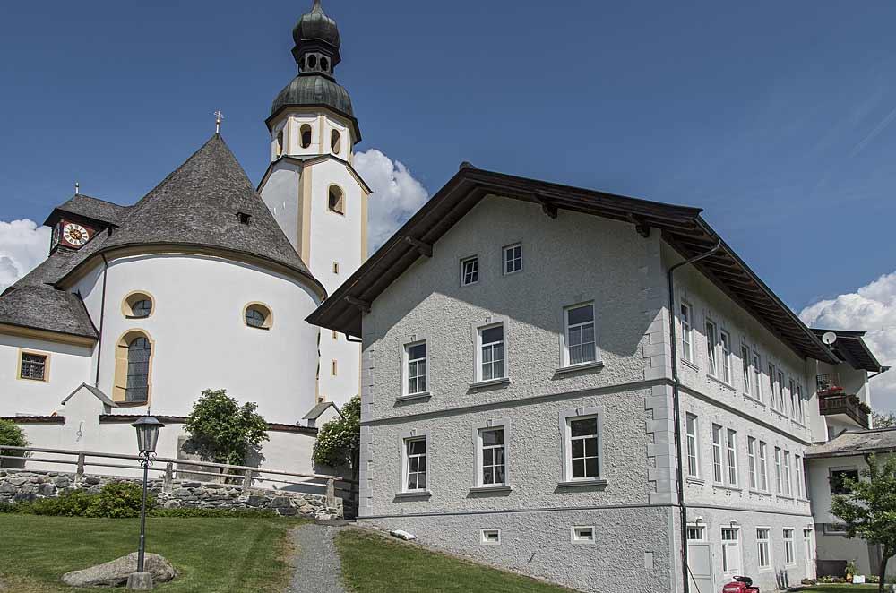 Bergbau- und Heimatmuseum Jochberg, im Hintergrund die Pfarrkirche St. Wolfgang
