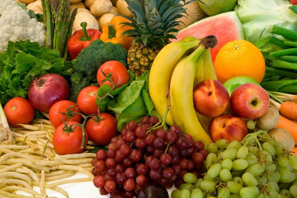 Rohes Obst und Gemüse, unteranderem: Bananen, Ananas, Trauben, Pfirsiche und Tomaten.