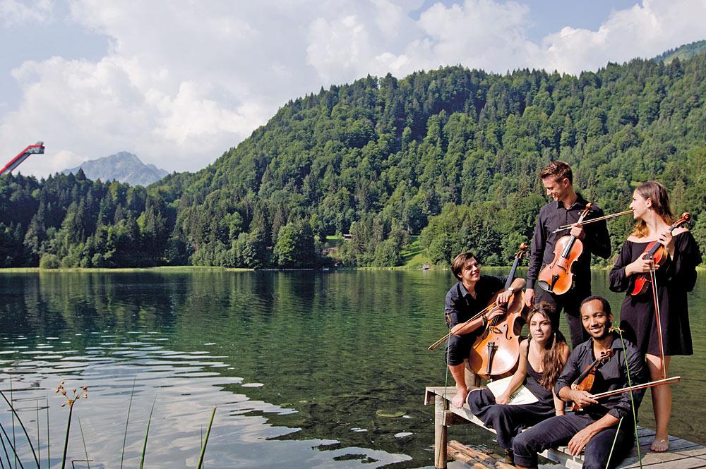 Streichergruppe auf dem Oberstdorfer Freibergsee, im Hintergrund die Heini-Klopfer-Schanze