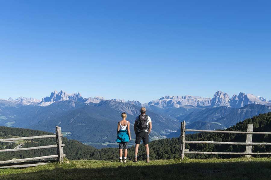 Zwei Wanderer stehen in der Landschaft der Dolomiten.