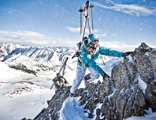 Frau klettert auf einen Bergipfel