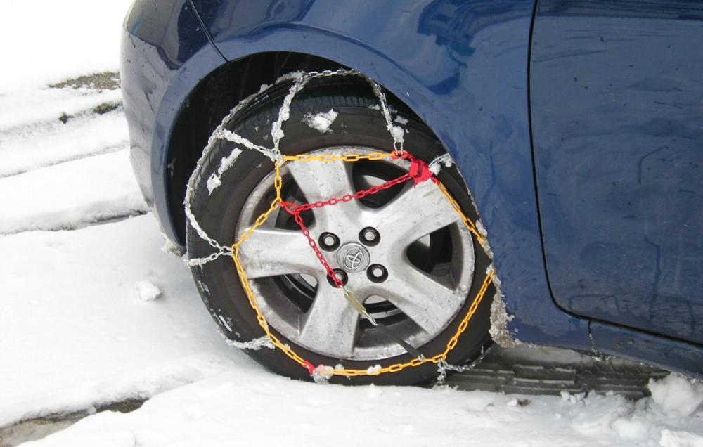 Auto mit aufgezogenen Schneeketten
