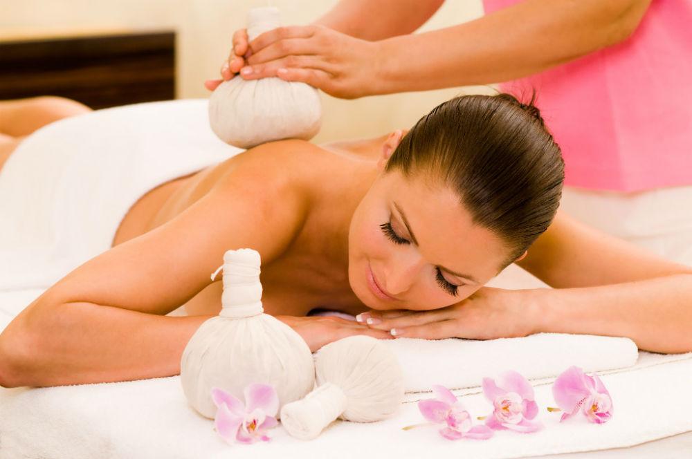 Eine Frau genießt eine Kräuterstempelmassage