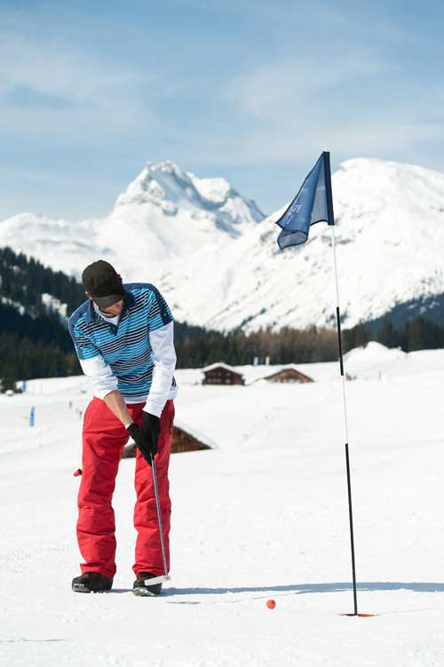 Golfer beim Einlochen auf einem Golfplatz im Winter
