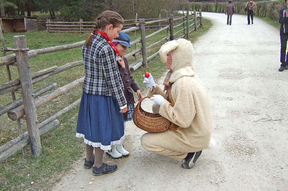 Osterhase schenkt Kindern Ostereiern im Salzburger Freilichtmuseum
