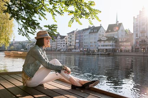 Eine Frau sitzt am Ufer der Limnmat und entspannt sich