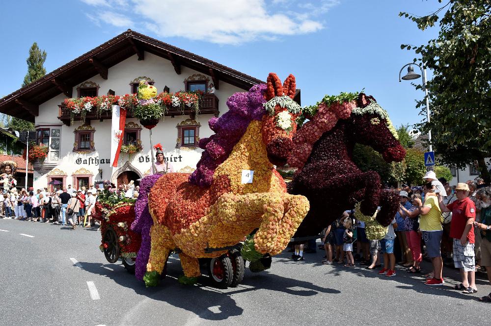 Ein Umzugswagen auf dem Blumenkorso umgeben von Zuschauern