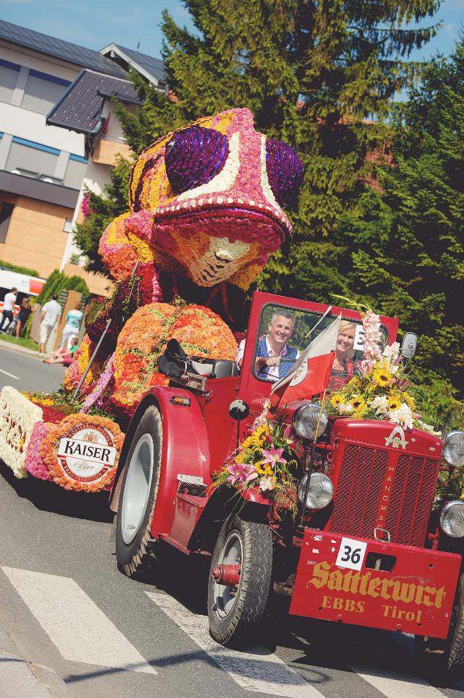 Ein Umzugswagen auf dem Blumenkorso Ebbs umgeben von Zuschauern