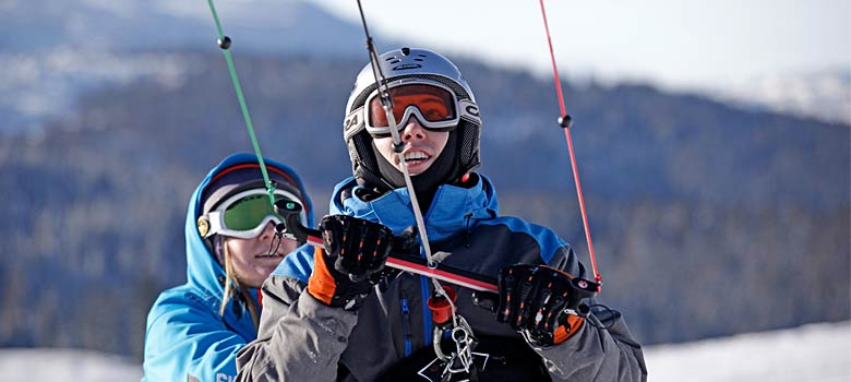 Snowkiterin hält die Handles des Kites fest