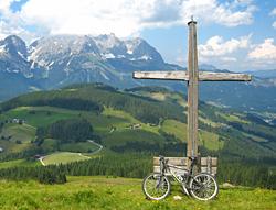 Wilder Kaiser mit Gipfelkreuz und E-Bike