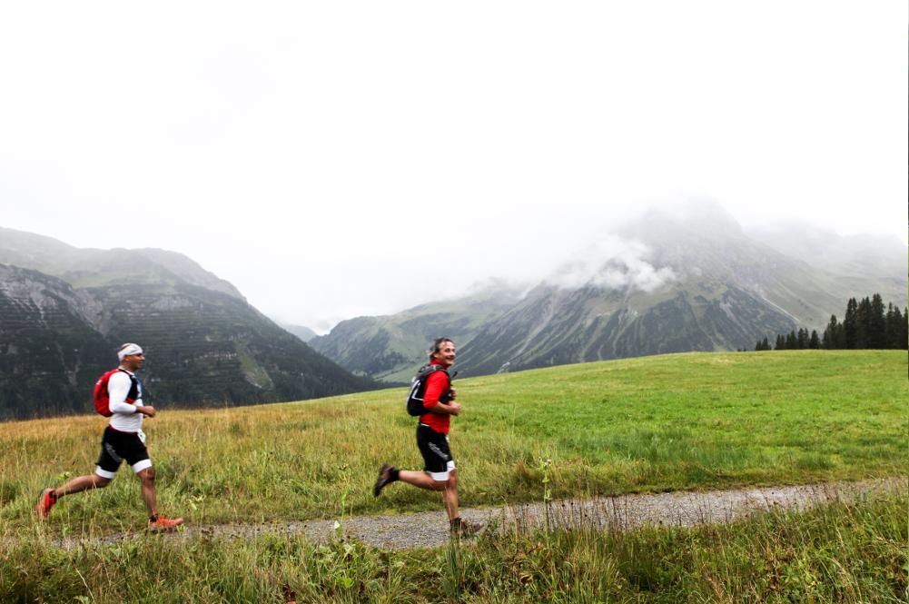 Zwei Läufer des Triathlons vor einer Bergkette der Alpen im Hintergrund