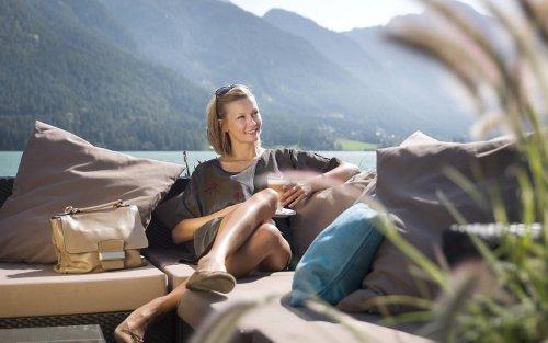 Frau entspannt mit einem Getränk auf einer Terrasse am Achensee