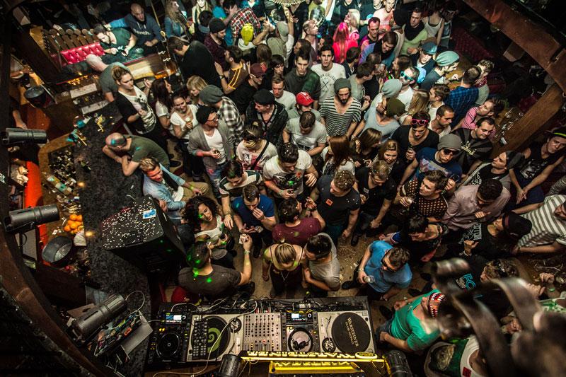 Blick von Galerie auf tanzende Raver und DJ-Pult