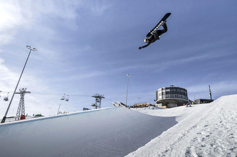 Snowboarder im LAAX Snowpark, im Hintergrund die Station GALAAXY