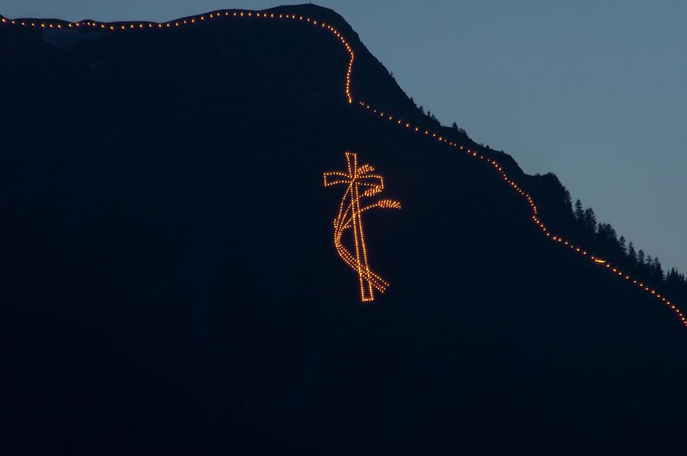 Bergfeuer in Kreuzform bei Nacht