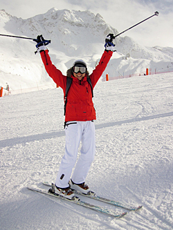 Skifahrerin die die Skistöcke nach oben hält auf ein Piste in den USA