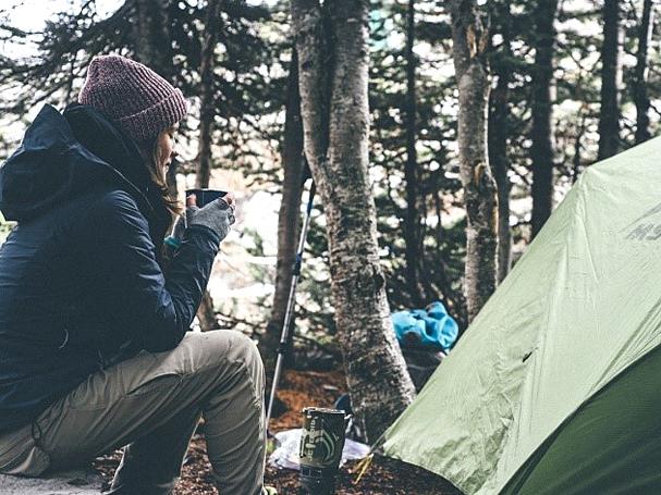 Frau neben einem Zelt