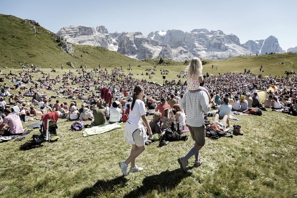 Zahlreiche Zuhörer sitzen auf den Bergwiesen der Dolomiten