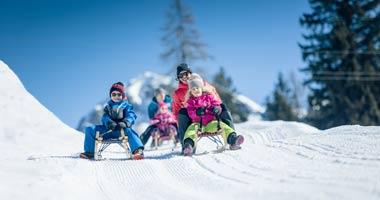 Familie beim Rodeln in Obertauern