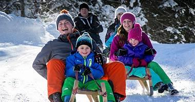 Familie beim Rodeln in der Salzburger Sportwelt