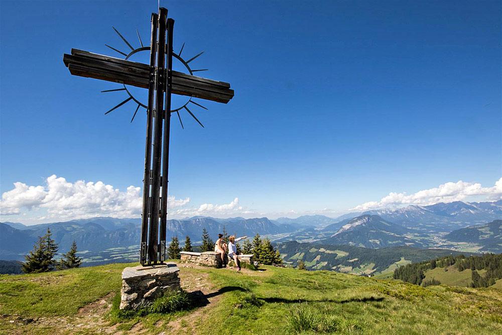 Wanderer unter dem Gipfelkreuz auf dem Rosskopf in der Wildschönau