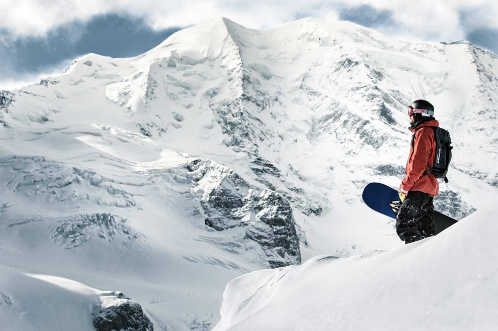Snowboarder mit Snowboard in der Hand in den Bergen der Corviglia