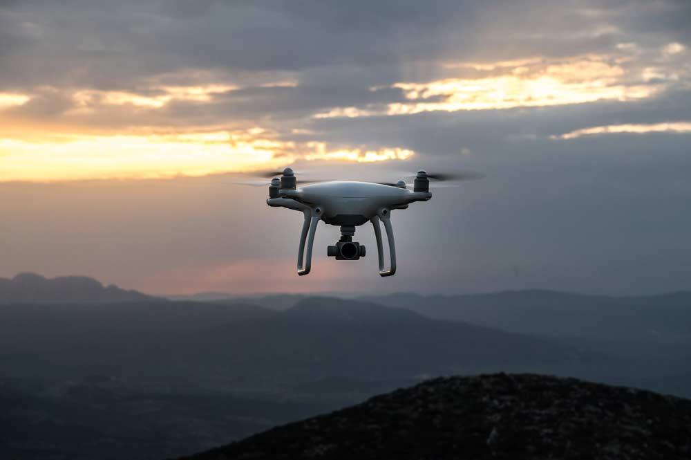 Eine Drohne beim Flug im Abendrot in den Bergen