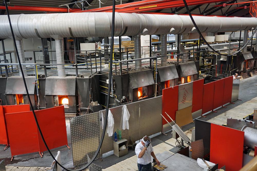 Blick in die Produktionshalle mit Öfen und offenen Feuern