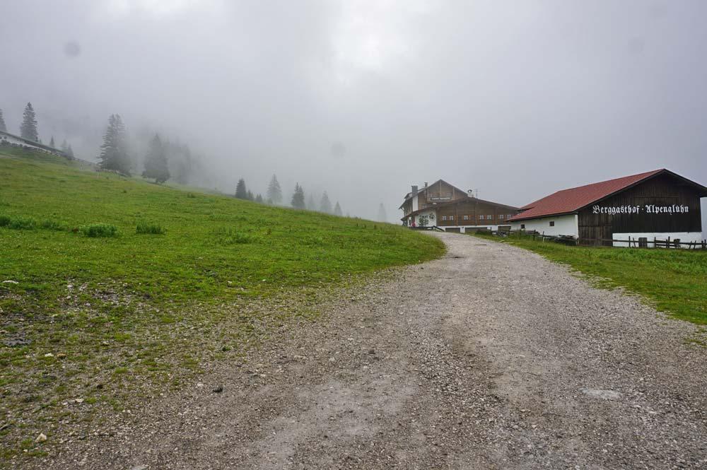 Blick auf einen breiten Wanderweg der am Gasthof Alpenglühen vorbei führt