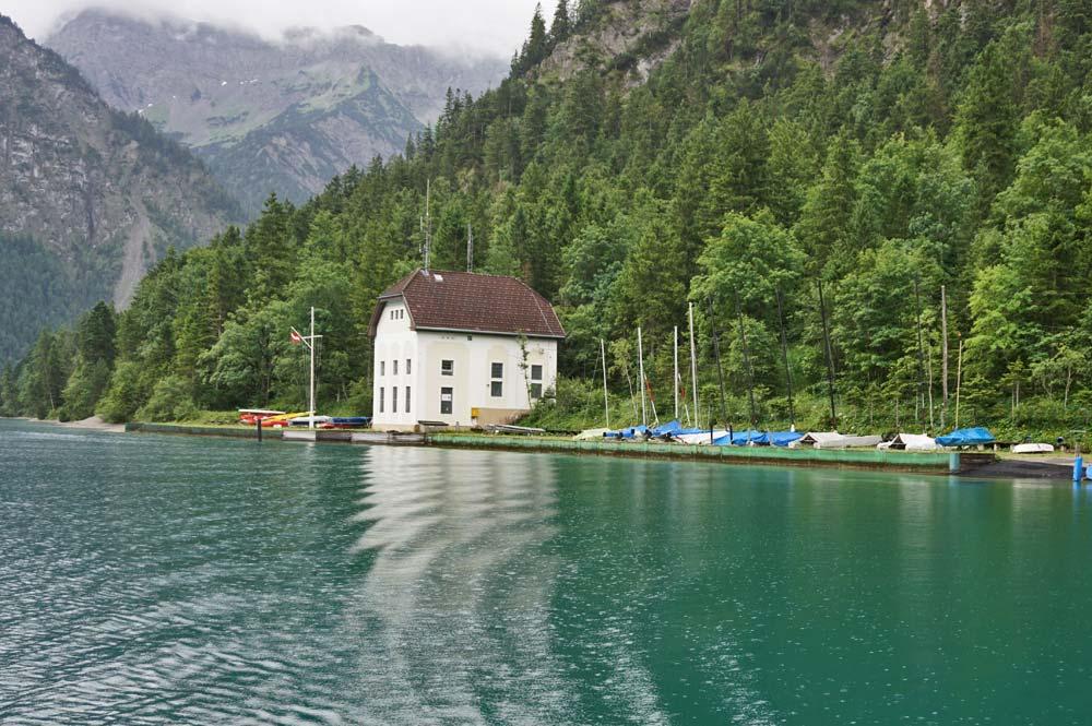 Blick zur Uferseite auf ein Haus am See mit Segelschiffen an der Anlegestelle