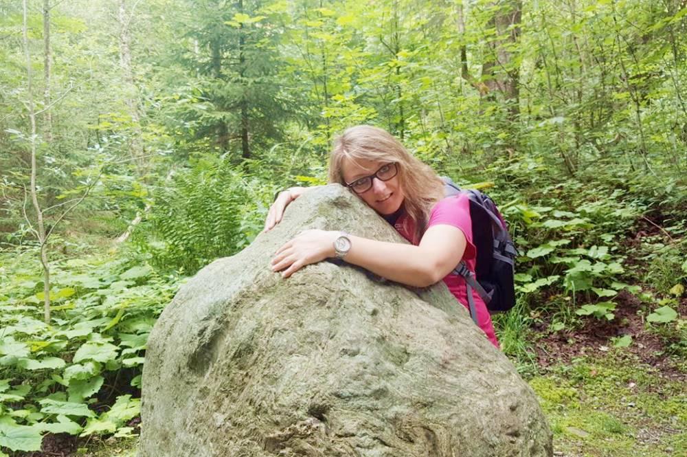 Wanderin umarmt den Stein der Weisheit am Weg der Besinnung in Alpbach