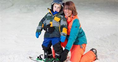 Mutter mit Kind beim Snowboarden