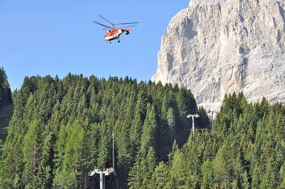 Ein Helikopter hilft bei der Montage der Seilbahnstahlstützen