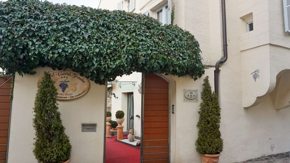 Mit Efeu umrankter Eingang des Hotel Traube in Brixen