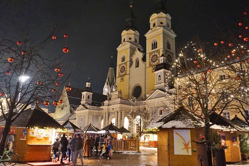 Weihnachtsmarkt auf dem Domplatz in Brixen vor dem beleuchteten Dom