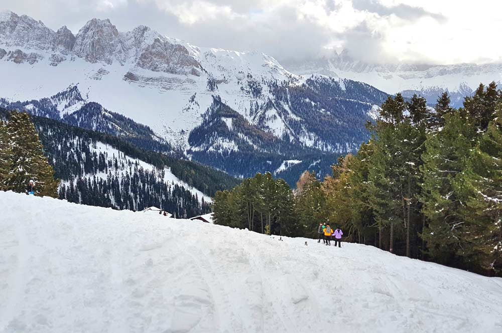 Schneeschuhwandern auf der Plose vor der verschneiten Bergkulisse der Dolomiten in der Nähe der Pfannspitzbahn