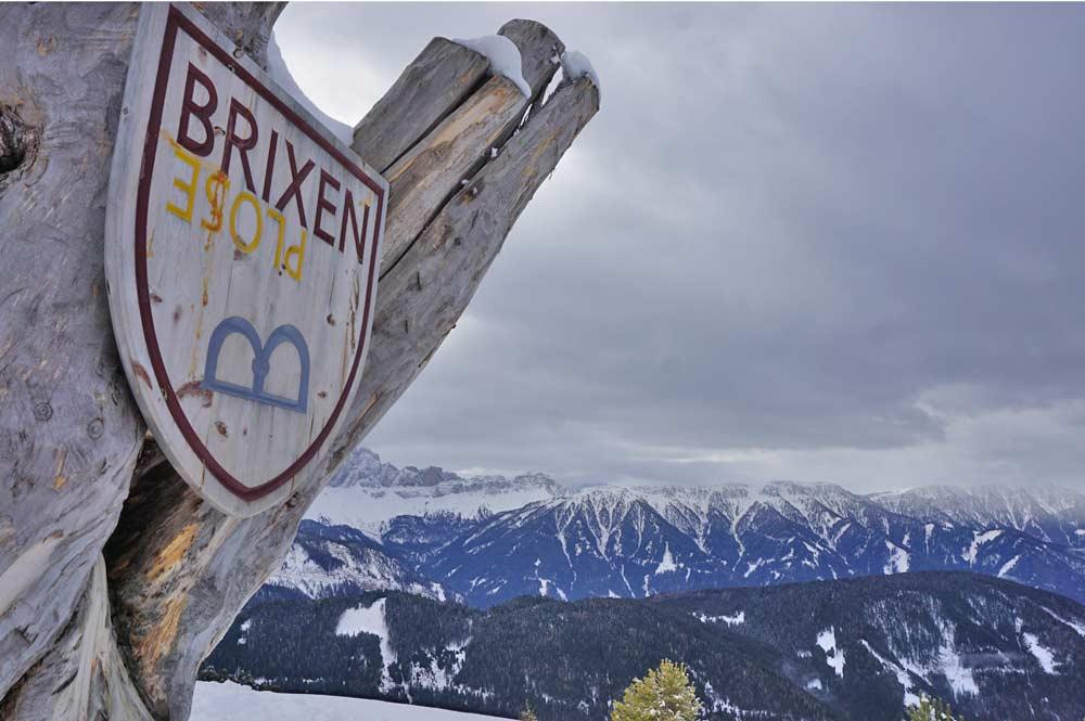 Baum mit Brixen-Plose Schild, eine Station des WoodyWalk
