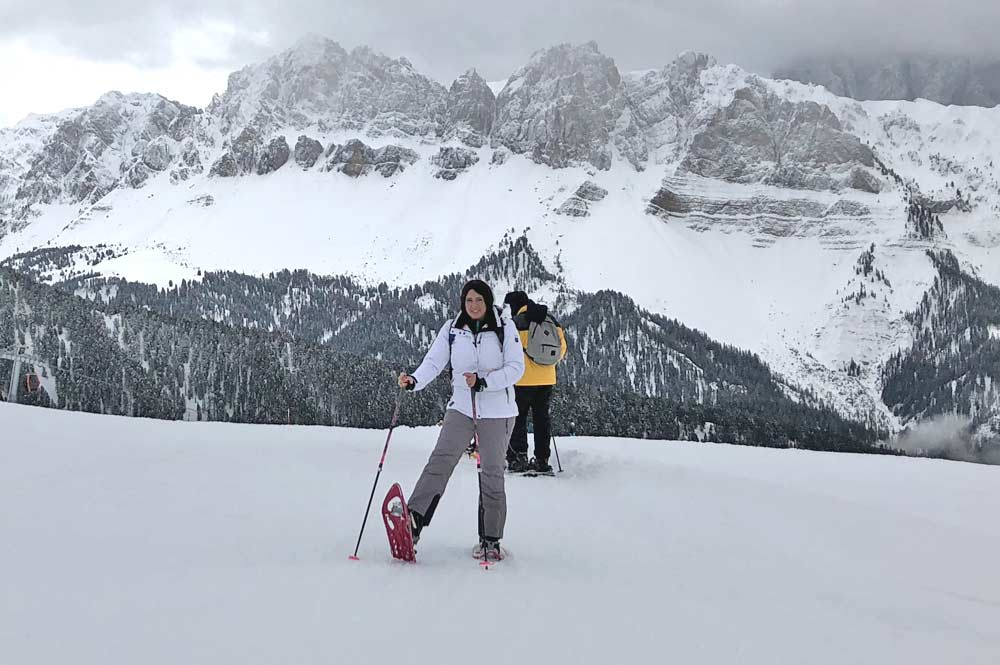 Kurze Rast bei der Schneeschuhwanderung, im Hintergrund das Bergpanorama der Dolomiten