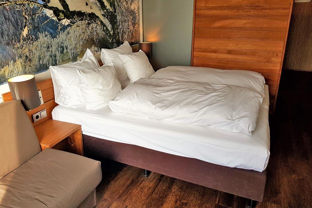 Gemütliches Doppelbett in einem der Hotelzimmer
