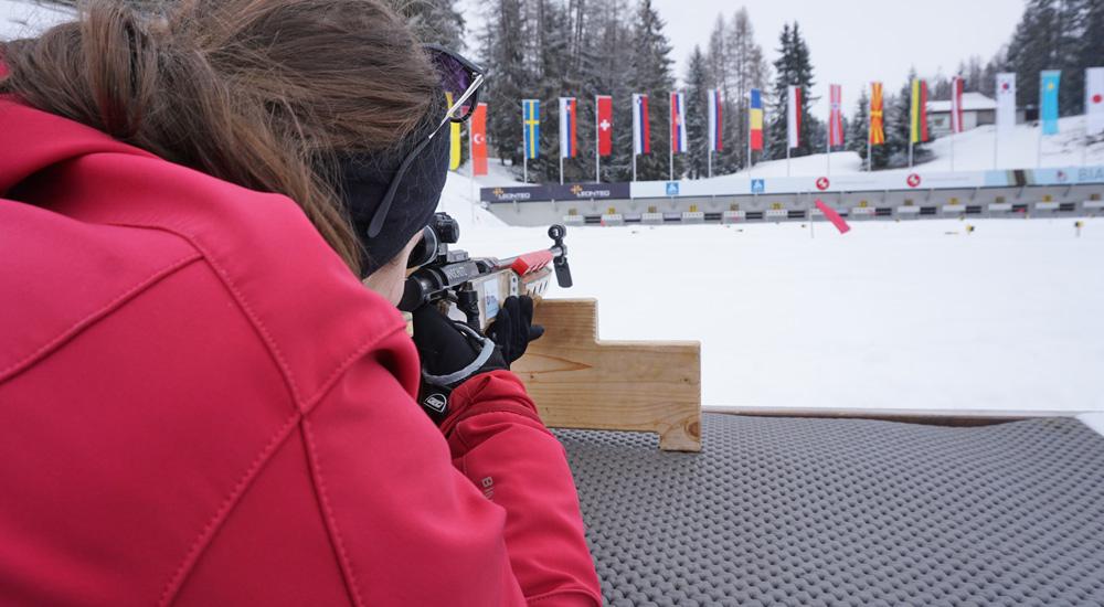 Anna mit Biathlon-Gewehr am Schießstand der Biathlon Arena Lenzerheide