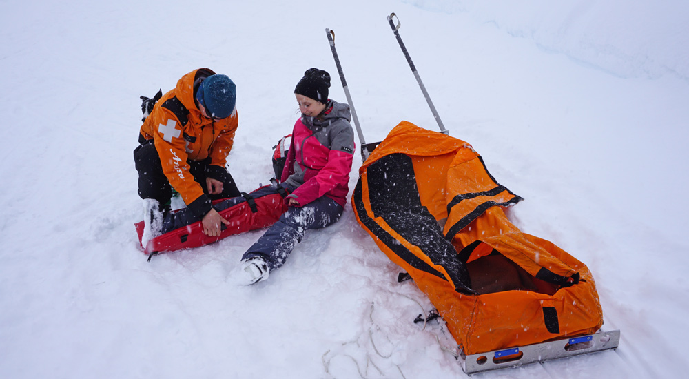 Bergretter Nico legt an einem Skifahrer eine Beinschiene an